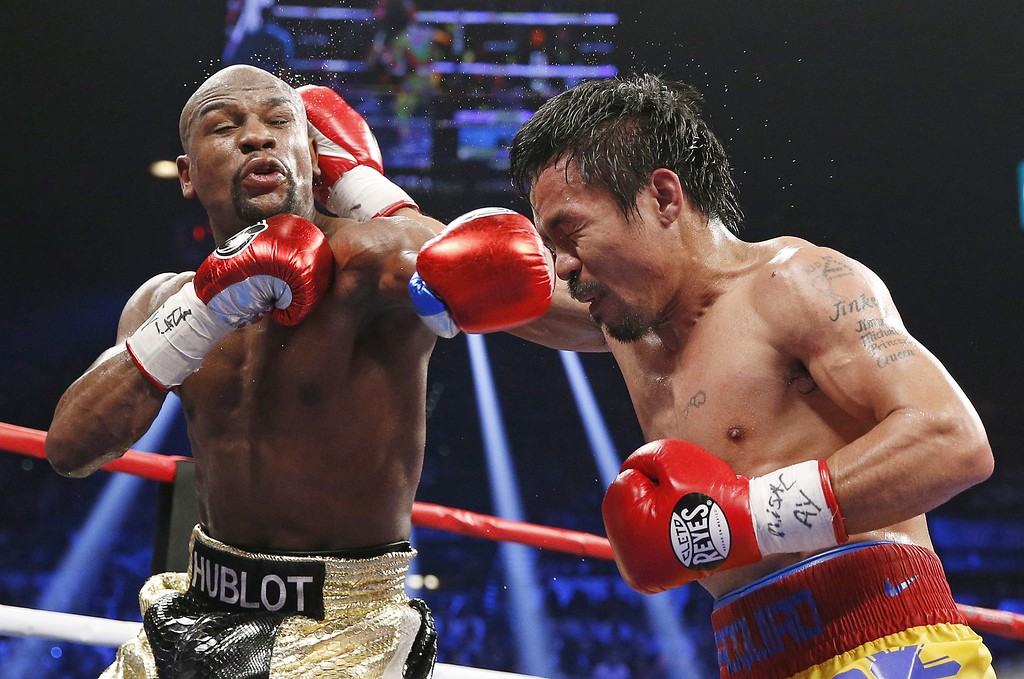 . Floyd Mayweather Jr., left, faces off with Manny Pacquiao, from the Philippines, during their welterweight title fight on Saturday, May 2, 2015 in Las Vegas. (AP Photo/John Locher)