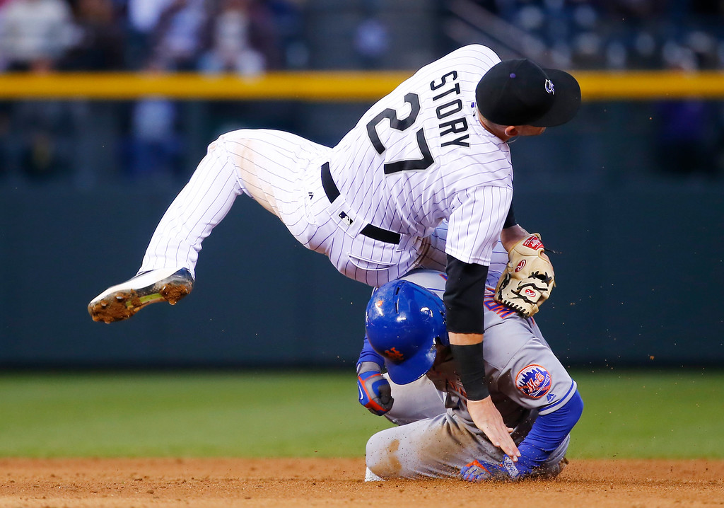 . New York Mets\' David Wright, bottom, is forced out at second as Colorado Rockies shortstop Trevor Story falls after throwing to first to complete the double play on Michael Conforto during the fifth inning of a baseball game Saturday, May 14, 2016, in Denver. (AP Photo/Jack Dempsey)
