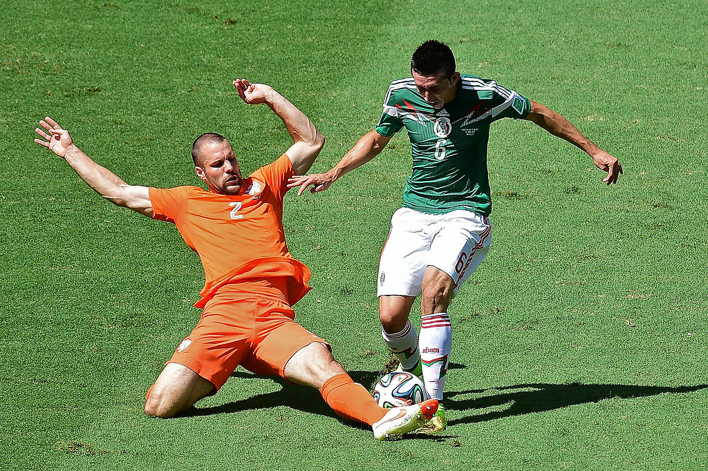 . Netherlands\' defender Ron Vlaar (L) vies with Mexico\'s midfielder Hector Herrera during a Round of 16 football match between Netherlands and Mexico at Castelao Stadium in Fortaleza during the 2014 FIFA World Cup on June 29, 2014.   JAVIER SORIANO/AFP/Getty Images