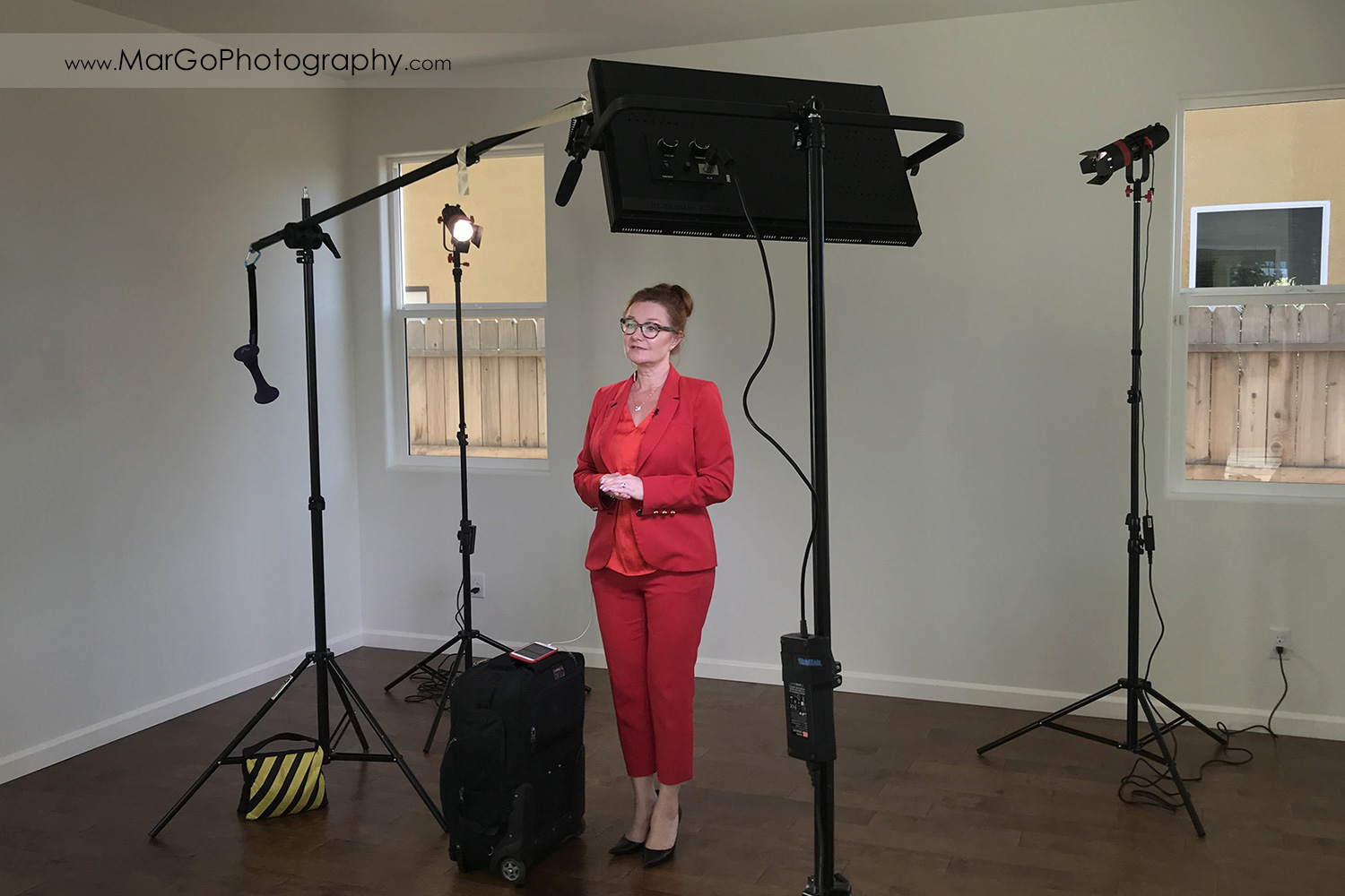 behind the scenes of indoor filming woman speaker in red suit seen through the lights and boom mic