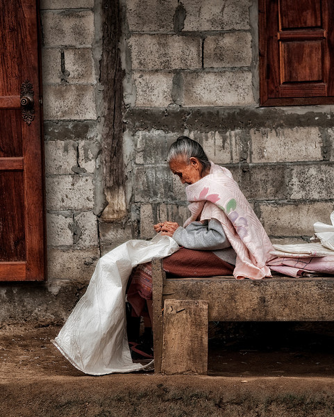 Old lady sewing in the small village of Naxao.  Laos, 2010.