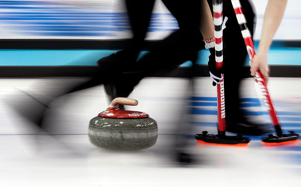 . Canada\'s Dawn McEwen, right, and Kaitlyn Lawes, left, sweep the ice during the women\'s curling competition at the 2014 Winter Olympics, Thursday, Feb. 13, 2014, in Sochi, Russia. (AP Photo/Wong Maye-E)