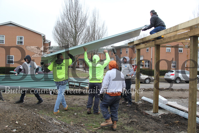 Members of Action in Recovery  work together to help lift a roofing panel onto the pavilion being built at Island Park on Saturday, March 2, 2019 while Sam Zurzolo,  Butler Township Vice-President Commissioner,  in the orange sweatershirt,  supervises. A.I.R. members from left to right: Alexander Robertson of Butler, Glenn Cummins of Butler, Mike Dienert of Butler, Zack Birckbichler of Butler, and Tom Lovic of Butler.Photos by Lauryn Halahurich/Butler Eagle