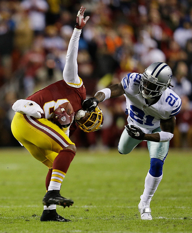 . Santana Moss #89 of the Washington Redskins is tackled  by Mike Jenkins #21 of the Dallas Cowboys after catching a pass in the first quarter at FedExField on December 30, 2012 in Landover, Maryland.  (Photo by Rob Carr/Getty Images)