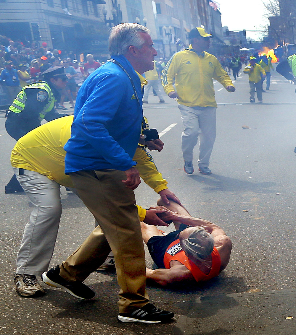 . People react to a second explosion at the 2013 Boston Marathon in Boston, Monday, April 15, 2013. Two explosions shattered the euphoria of the Boston Marathon finish line on Monday, sending authorities out on the course to carry off the injured while the stragglers were rerouted away from the smoking site of the blasts. (AP Photo/The Boston Globe,  John Tlumacki)