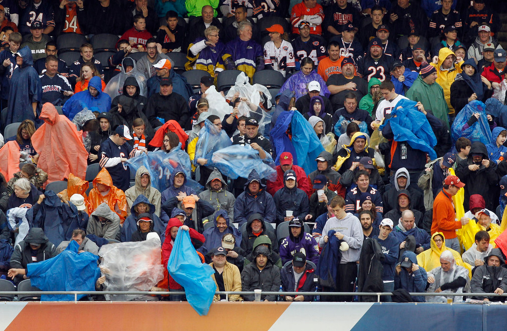 . Fan start to put rain gear on as rain begins to fall at Soldier Field during the first half of an NFL football game between the Chicago Bears and Baltimore Ravens, Sunday, Nov. 17, 2013, in Chicago. (AP Photo/Kiichiro Sato)