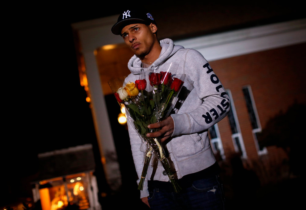 Description of . Anthony Baracey holds flowers honoring victims of the Sandy Hook Elementary school killing before a vigil at the Saint Rose of Lima church in Newtown, Connecticut December 14, 2012. A heavily armed gunman opened fire on school children and staff at a Connecticut elementary school on Friday, killing at least 26 people, including 20 children, in the latest in a series of shooting rampages that have tormented the United States this year.  REUTERS/Shannon Stapleton