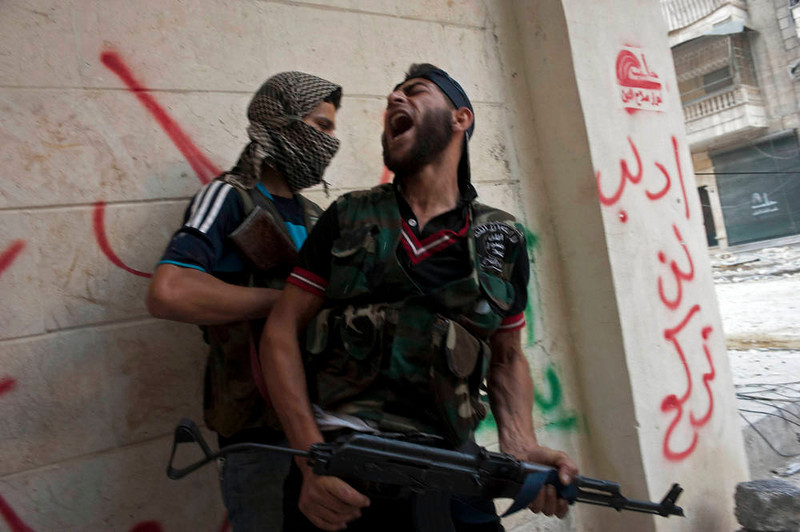 . Free Syrian Army fighters take cover as they exchange fire with regime forces in the Salaheddin neighbourhood of Syria\'s northern city of Aleppo on August 22, 2012. At least 12 people were killed in a raid on a district of Damascus, while fighter jets and artillery pummelled the city of Aleppo and rebels claimed seizing parts of a town on the Iraqi border, a watchdog said. AFP PHOTO / JAMES  LAWLER DUGGAN/AFP/Getty Images