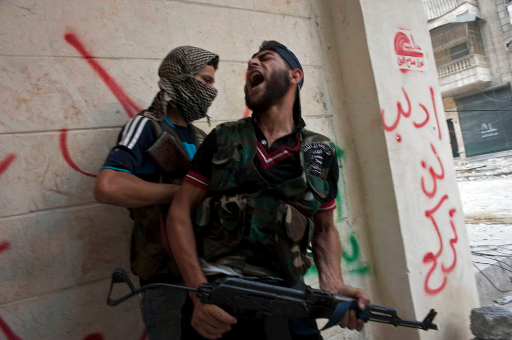 Description of . Free Syrian Army fighters take cover as they exchange fire with regime forces in the Salaheddin neighbourhood of Syria's northern city of Aleppo on August 22, 2012. At least 12 people were killed in a raid on a district of Damascus, while fighter jets and artillery pummelled the city of Aleppo and rebels claimed seizing parts of a town on the Iraqi border, a watchdog said. AFP PHOTO / JAMES  LAWLER DUGGAN/AFP/Getty Images