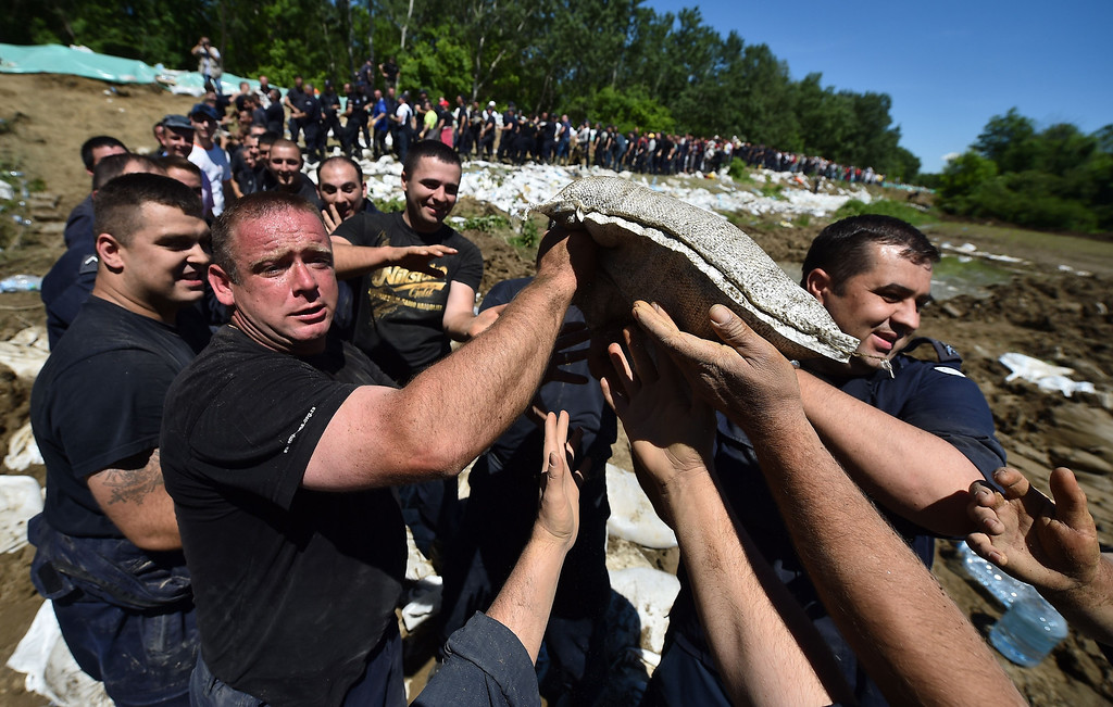 . Volunteers and police officers pass sandbags to reinforce the bank of the river Sava near Sabac, 100 kilometers west of Belgrade, on May 19, 2014. The Balkans braced for more misery as the death toll from the worst floods in a century rose to 47 and rising waters forced thousands more to flee their homes. Muddy waters from the Sava River have submerged houses, churches, mosques and roads in Bosnia, Serbia and Croatia after record rainfall wreaked havoc across the central European region. AFP PHOTO / ANDREJ ISAKOVIC/AFP/Getty Images