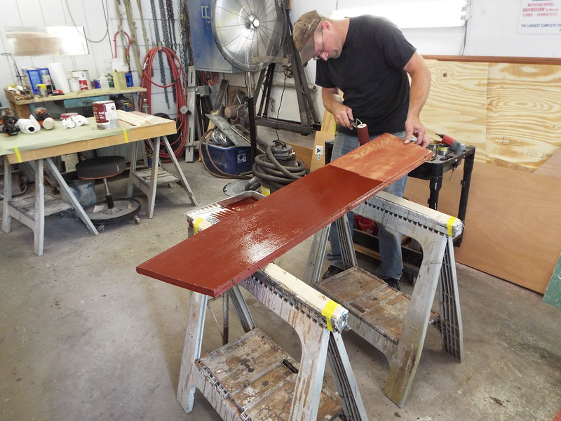 Painting the front foot rest to seal the wood before the upholstery is applied.