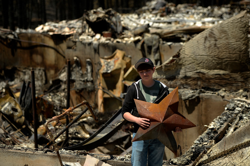 . COLORADO SPRINGS, CO. - June 19: Nolan Schultz 16 carries a surviving ornament from his families home of 8 years. Nolan had not seen the damage and was very affected by the loss. More residents were allowed back to see their homes that were burned in the Black Forest Fire area near Colorado Springs, Colorado. June 19, 2013 Colorado Springs. (Photo By Joe Amon/The Denver Post)