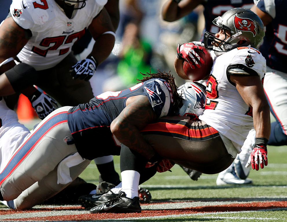 . New England Patriots middle linebacker Brandon Spikes (55) tackles Tampa Bay Buccaneers running back Doug Martin (22) in the first half of an NFL football game Sunday, Sept. 22, 2013, in Foxborough, Mass. (AP Photo/Elise Amendola)