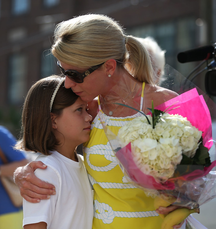 . Joanna Ghegan hugs her daughter, Grace Ghegan,9, before they lay flowers in front of Emanuel African Methodist Episcopal Church after a mass shooting at the church that killed nine people of June 19, 2015. A 21-year-old white gunman is suspected of killing nine people during a prayer meeting in the church, which is one of the nation\'s oldest black churches in Charleston. (Photo by Joe Raedle/Getty Images)