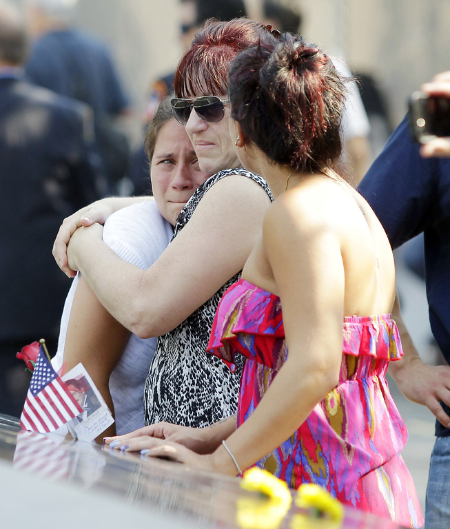 . Mourners reacts at the 9/11 Memorial during ceremonies for the twelfth anniversary of the terrorist attacks on lower Manhattan at the World Trade Center site on September 11, 2013 in New York City.  (Photo by Mary Altaffer-Pool/Getty Images)