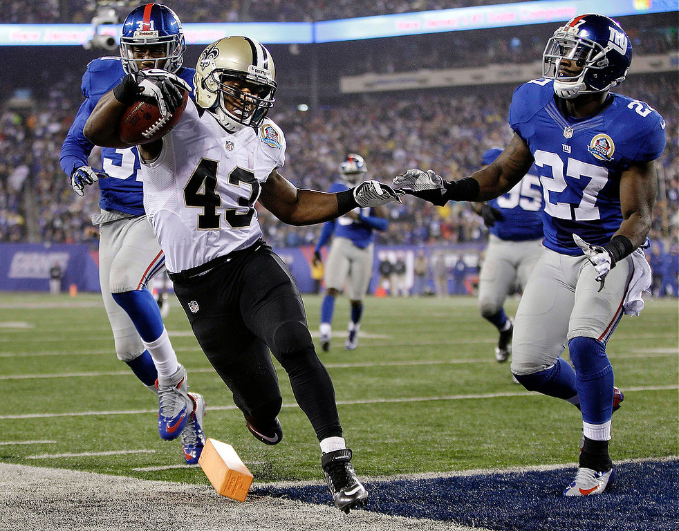 . New Orleans Saints running back Darren Sproles (43) scores on a 9-yard touchdown run ahead of New York Giants defensive back Will Hill (31) and Stevie Brown (27) during the second half of an NFL football game, Sunday, Dec. 9, 2012, in East Rutherford, N.J. (AP Photo/Kathy Willens)