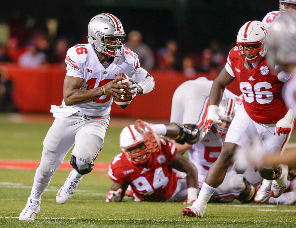 . Ohio State quarterback J.T. Barrett (16) scrambles past Nebraska defensive linemen Carlos Davis (96) and Khalil Davis (94) during the first half of an NCAA college football game in Lincoln, Neb., Saturday, Oct. 14, 2017. (AP Photo/Nati Harnik)