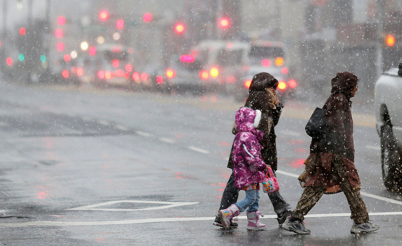 . Snow falls as people cross Broad Street in downtown Newark, N.J., Wednesday, Dec. 26, 2012. The National Weather Service forecast sustained winds of 15 to 20 mph along the coast in the afternoon, with gusts up to 40 mph. The storm is expected to dump a total of four to six inches on the area and also produce sleet and freezing rain. Other areas are expected to get between two and three inches of rain. A flood watch has been issued from Wednesday afternoon through Thursday morning. (AP Photo/Julio Cortez)