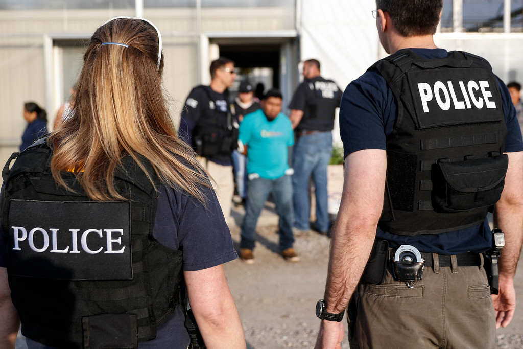 . Government agents take a suspect into custody during an immigration sting at Corso\'s Flower and Garden Center, Tuesday, June 5, 2018, in Castalia, Ohio. The operation is one of the largest against employers in recent years on allegations of violating immigration laws. (AP Photo/John Minchillo)