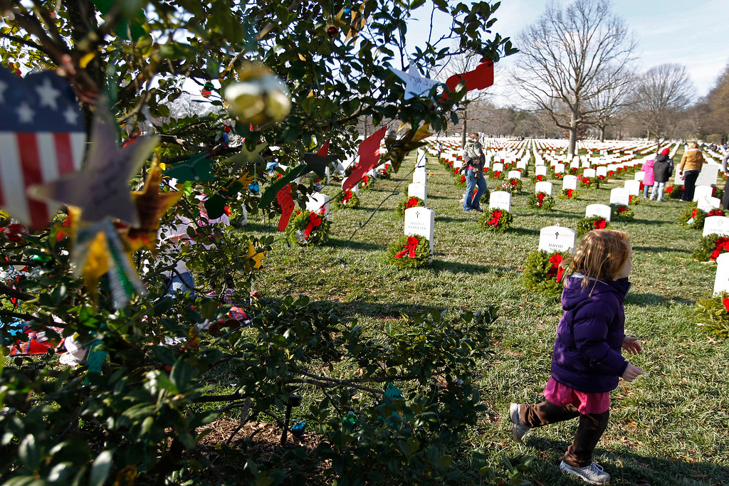 . A girl plays near a decorated holly tree as volunteers UPDATED Washington Photos Plan for Saturday, Dec. 10, 2011