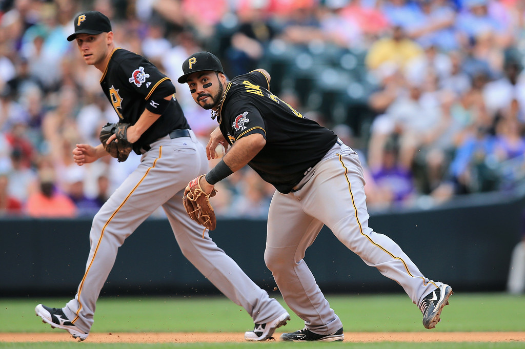 . Third baseman Pedro Alvarez #24 of the Pittsburgh Pirates makes a throwing error on a ground ball by Corey Dickerson #6 of the Colorado Rockies that allowed Yorvit Torrealba #8 of the Colorado Rockies to score and even the game at 2-2 as shortstop Clint Barmes #12 of the Pittsburgh Pirates backs up the play in the sixth inning at Coors Field on August 11, 2013 in Denver, Colorado. The Rockies defeated the Pirates 3-2.  (Photo by Doug Pensinger/Getty Images)