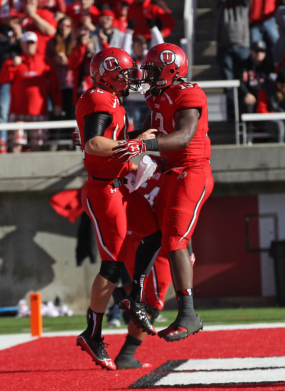 . Utah running back Kelvin York (13) celebrates with Utah quarterback Adam Schulz, left, after scoring against Colorado in the first half during an NCAA college football game Saturday, Nov. 30, 2013, in Salt Lake City. (AP Photo/Rick Bowmer)