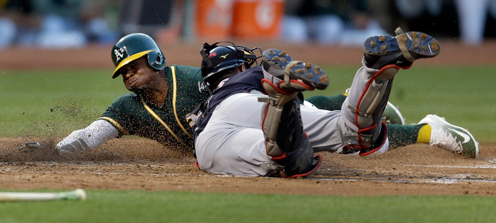 . Oakland Athletics\' Rajai Davis, left, scores past Cleveland Indians catcher Yan Gomes during the third inning of a baseball game Friday, July 14, 2017, in Oakland, Calif. (AP Photo/Ben Margot)