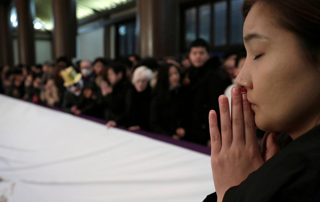 . A woman prays at the start of the New Year at Zojoji Buddhist temple in Tokyo, early Wednesday, Jan. 1, 2014. (AP Photo/Shizuo Kambayashi)