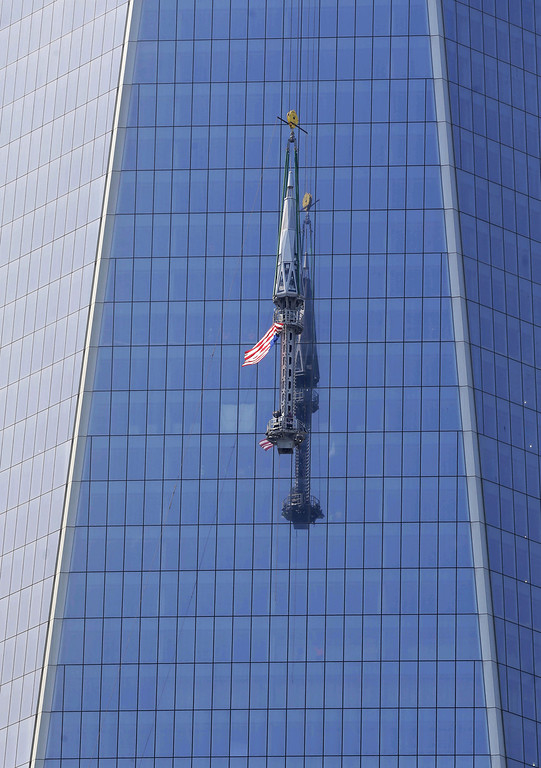 . The top piece of the 408-foot spire for One World Trade Center is lifted to the top of the building in New York, Thursday, May 2, 2013.   (AP Photo/Seth Wenig)