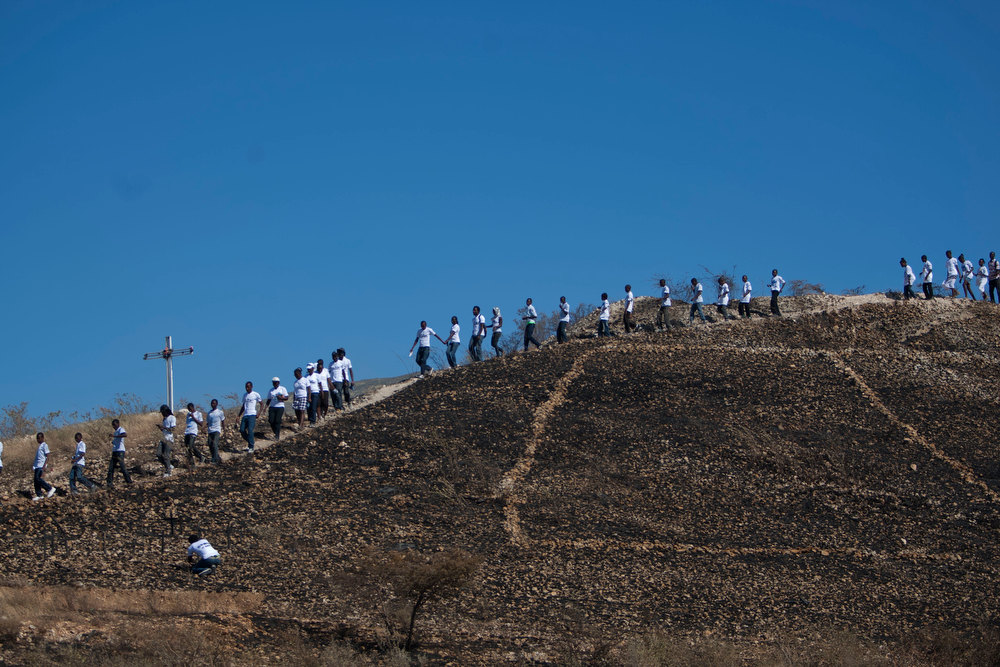 Description of . Relatives of those who died in the 2010 earthquake descend a hilltop prior to a memorial service at Titanyen, a mass burial site north of Port-au-Prince, Haiti, Saturday, Jan. 12, 2013. Haitians recalled the tens of thousands of people who lost their lives in a devastating earthquake three years ago, marking the disaster\'s anniversary Saturday with a simple ceremony. Haiti\'s previous presidential administration said 316,000 people were killed but no one really knows how many died.  (AP Photo/Dieu Nalio Chery)