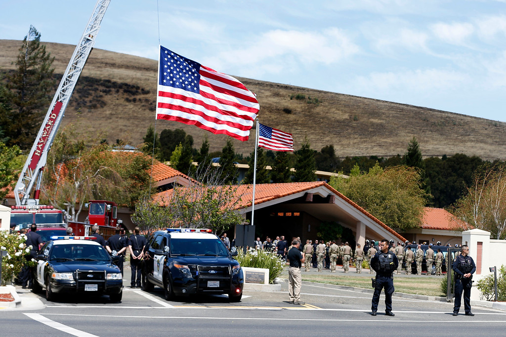 . Police officers from several law enforcement agencies and firefighters stand guard as they prepare to salute the body of Hayward police Sgt. Scott Lunger brought in a coffin during the procession from the Coroner\'s Bureau in Oakland to Chapel of the Chimes Memorial Park in Hayward, Calif., on Thursday, July 23, 2015. Lunger was killed during a traffic stop in early Wednesday. (Ray Chavez/Bay Area News Group)