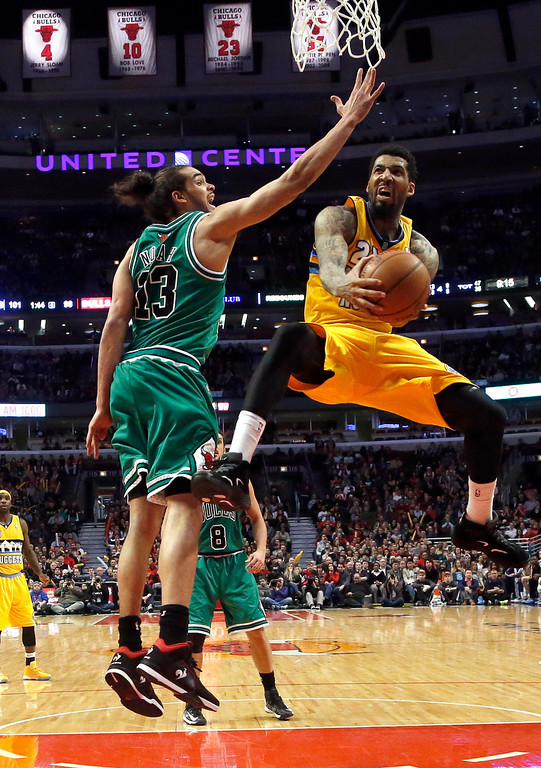 . Denver Nuggets guard Wilson Chandler (21) shoots past Chicago Bulls center Joakim Noah during the second half of an NBA basketball game, Monday, March 18, 2013, in Chicago. The Nuggets won 119-118 in overtime. (AP Photo/Charles Rex Arbogast)