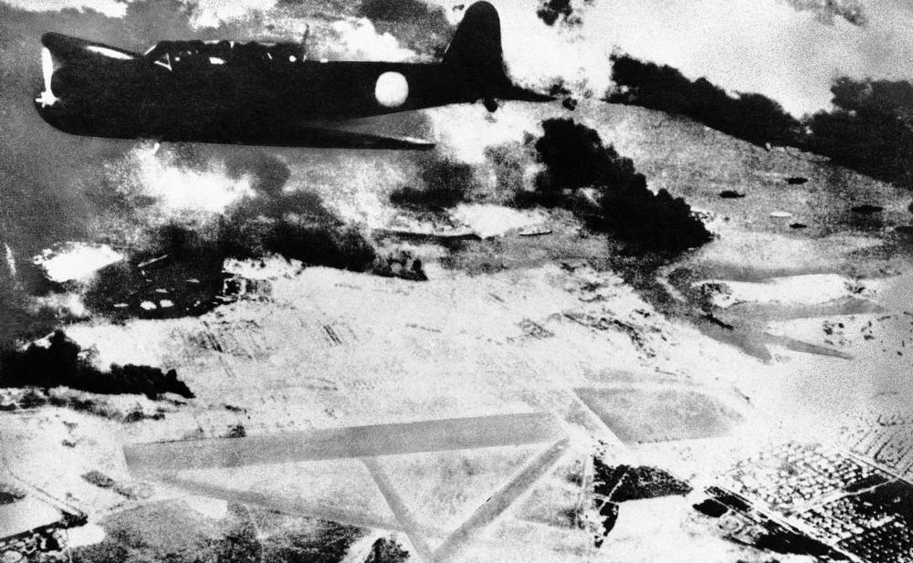 Description of . A Japanese bomber on a run over Pearl Harbor, Hawaii is shown during the surprise attack of Dec. 7, 1941. Black smoke rises from American ships in the harbor. Below is a U.S. Army air field.  (AP Photo)