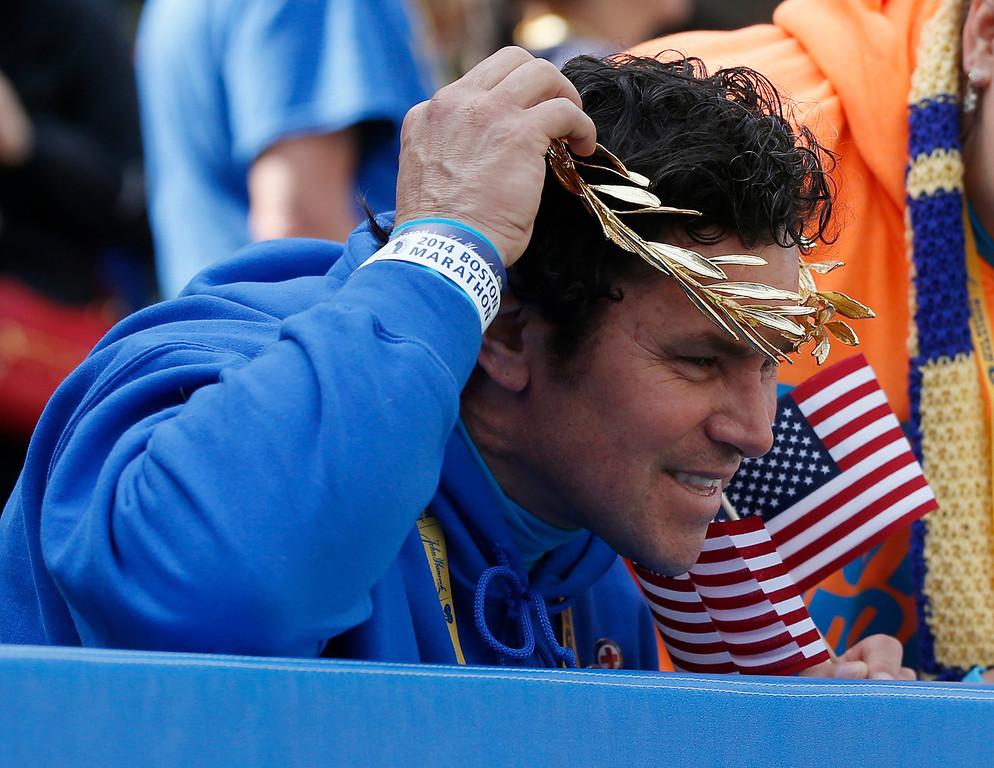 . Boston Marathon bombing hero Carlos Arredondo tries on a victor\'s wreath near the finish line of the 118th Boston Marathon Monday, April 21, 2014 in Boston. (AP Photo/Elise Amendola)