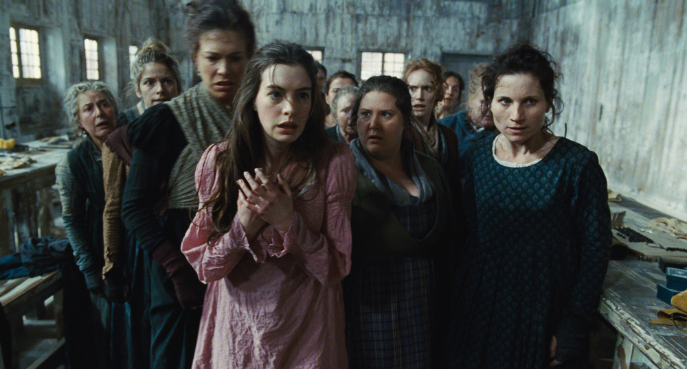 Description of . This undated publicity photo provided by Universal Pictures shows Anne Hathaway, left, as Fantine, being thrown out of the factory in a scene from director, Tom Hooper's new film,