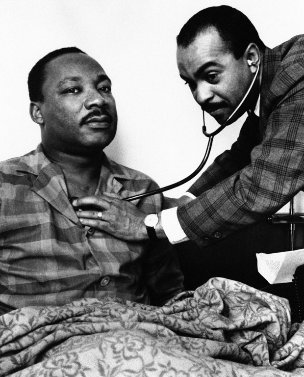 . Dr. Martin Luther King, Jr., head of the Southern Christian Leadership Conference, sits up in his hotel room bed in Philadelphia, Feb. 10, 1968 while being examined by Dr. Walter Lomax, a Philadelphia physician. On the physician\'s orders Dr. King canceled his appointments and speaking engagements for the day because of a throat ailment. Dr. King has been in Philadelphia for past two days recruiting followers for proposed march on the nation\'s capital in April. (AP Photo)
