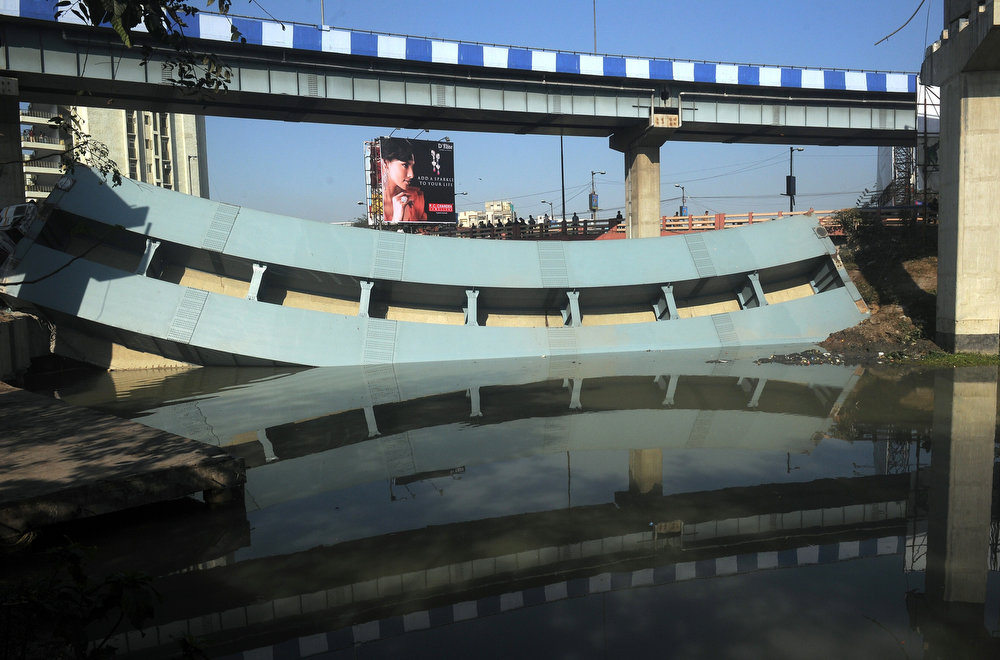 . Indian onlookers stand near the collapsed portion of a flyover in Kolkata on March 3, 2013. A huge portion of a flyover on the eastern side of the Indian metropolis collapsed leaving three persons injured, the flyover connects the airport with Eastern Metropolitan Bypass and the eastern and southern suburbs.   As the debris fell into a canal running below the flyover, it took down a truck the driver and two others were rescued from the canal by fire-brigade personnel and locals.  DIBYANGSHU SARKAR/AFP/Getty Images