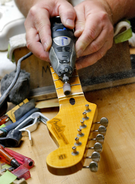 . The nut is filed on a new Fender Stratocaster electric guitar in the Fender Custom Shop in Corona, Calif. on Tuesday, Oct. 15, 2013. Leo Fender\'s Stratocaster turns 60 in 2014. (AP Photo/Matt York)