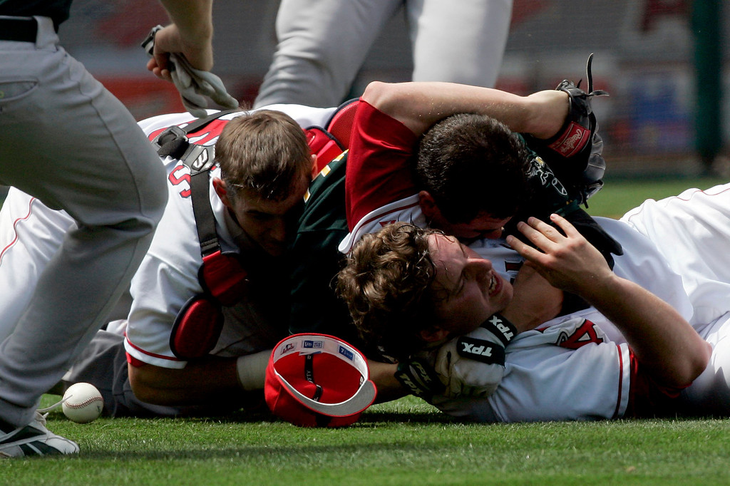 . Los Angeles Angels starting pitcher John Lackey, right, and catcher Jeff Mathis, left, brawl with Oakland Athletics\' Jason Kendall after Kendall rushed the mound during the sixth inning of their baseball game Tuesday, May 2, 2006, in Anaheim, Calif. (AP Photo/Chris Carlson)