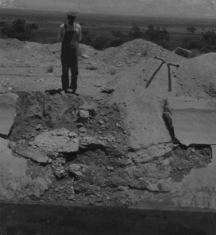 . A guard stands over the six-foot concrete wall of the L.A. aqueduct which was shattered by dynamite, eight miles below the Alabama Hills dam. This is the fourth blast within the month. Photo dated: June 20, 1927.  (Los Angeles Public Library)