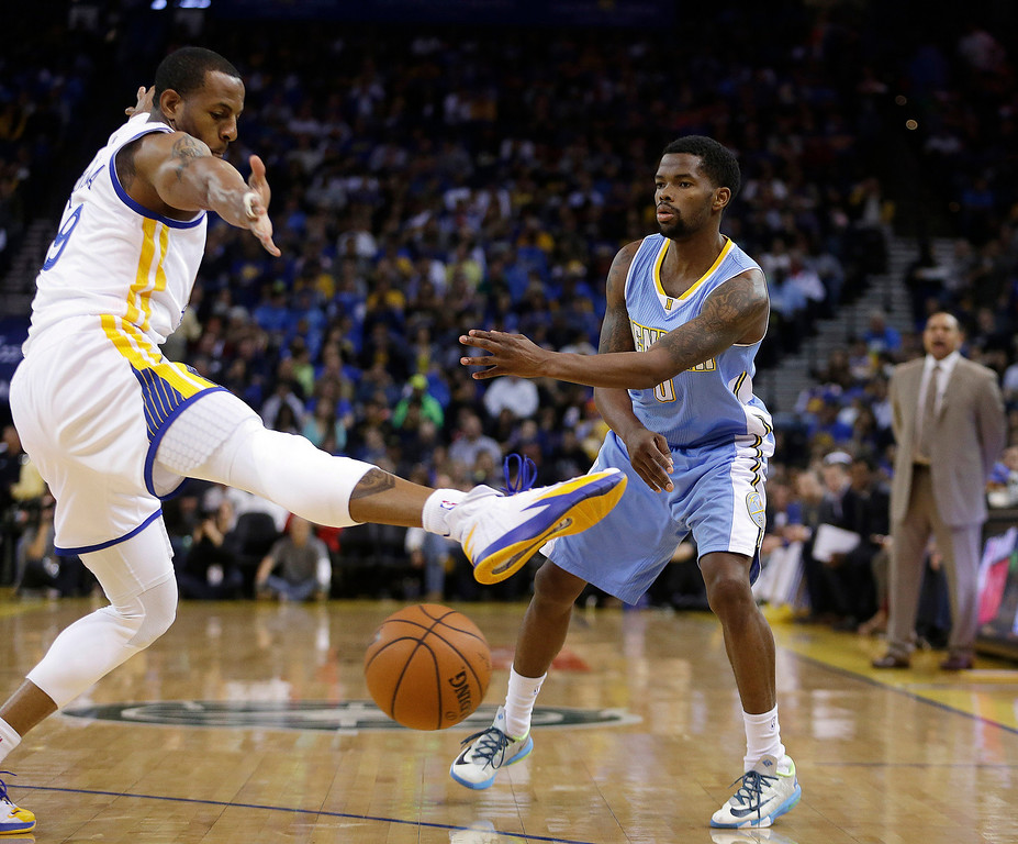 . Denver Nuggets\' Aaron Brooks, right, passes below the leg of Golden State Warriors\' Andre Iguodala during the first half of an NBA basketball game Thursday, April 10, 2014, in Oakland, Calif. (AP Photo/Ben Margot)