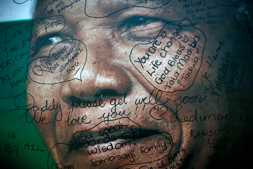. Messages left by supporters are seen on poster depicting former South African President Nelson Mandela set outside his Soweto home, outside of Johannesburg, South Africa, Thursday July 18, 2013. South Africa celebrated Nelson Mandela\'s 95th birthday with acts of charity on Thursday, a milestone capped by news that the former president\'s health was improving after fears that he was close to death during ongoing hospital treatment. (AP Photo/Jerome Delay)