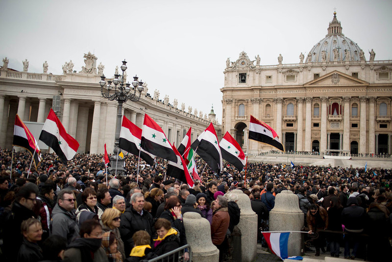 """. Faithful gather in St. Peter\'s Square as Syrian flags are waved, following Pope Francis\' Angelus at the Vatican, Sunday, March 17, 2013. Breaking with tradition, Pope Francis delivered off-the-cuff remarks about God\'s power to forgive instead of reading from a written speech for the first Sunday window appearance of his papacy. He also spoke only in Italian, beginning with \""""buon giorno\"""" (Good day) and ending with \""""buon pranzo\"""" (Have a good lunch), instead of greeting the faithful in several languages as his last few predecessors had done. (AP Photo/Oded Balilty)"""