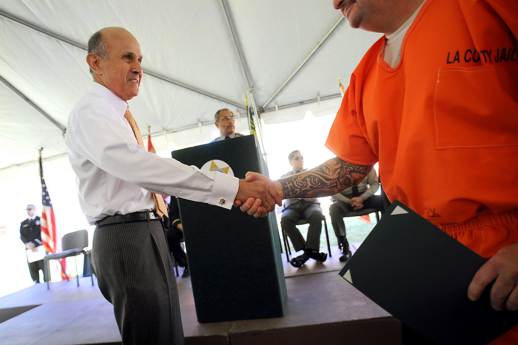 . LASD Sheriff Lee Baca congratulates a fire camp inmate during the first graduation ceremony for the new inmate fire training program at the Pitchess Detention Center in Castaic, CA November 19, 2012. The graduation ceremony was held for the 110 inmates who completed the new program. (Andy Holzman/L.A. Daily News)