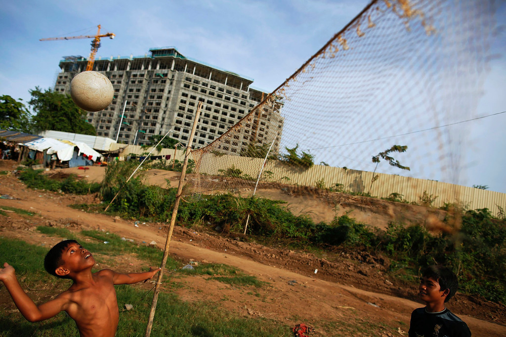 . Ethnic Cham Muslim children play volleyball in front of a hotel under construction on the banks of Mekong river in Phnom Penh July 30, 2013. About 100 ethnic Cham families, made up of nomads and fishermen without houses or land who arrived at the Cambodian capital in search of better lives, live on their small boats on a peninsula where the Mekong and Tonle Sap rivers meet, just opposite the city\'s centre. The community has been forced to move several times from their locations in Phnom Penh as the land becomes more valuable. They fear that their current home, just behind a new luxurious hotel under construction at the Chroy Changva district is only temporary and that they would have to move again soon.   REUTERS/Damir Sagolj