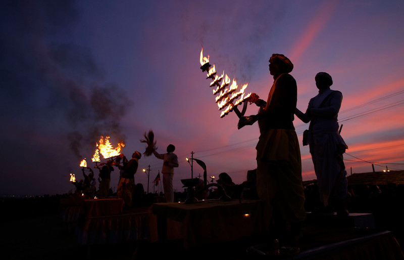 . Indian Hindu priests rotate traditional oil lamps as they perform evening rituals at the Sangam, the confluence of rivers Ganges, Yamuna, and mythical Saraswati rivers, during the annual traditional fair \'Magh Mela\' in Allahabad, India, Tuesday, Jan. 28, 2014. Hundreds of thousands of devout Hindus are expected to take holy dips at the confluence during the astronomically auspicious period of over 45 days celebrated as Magh Mela. (AP Photo/Rajesh Kumar Singh)