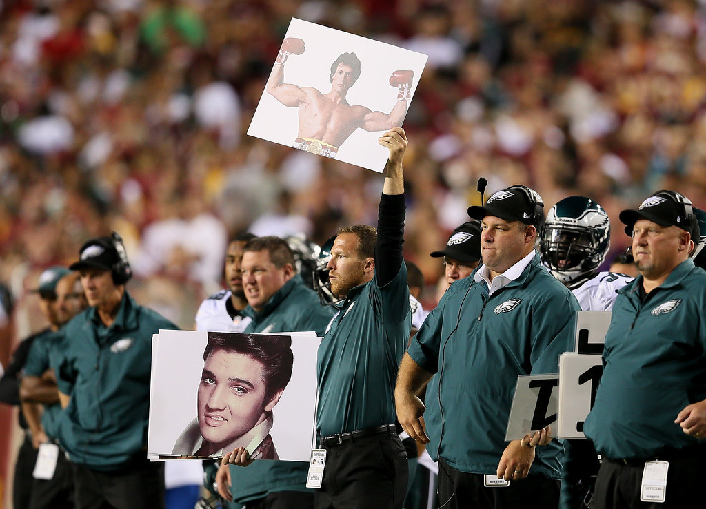 . Philadelphia Eagles coaches hold up Rocky and Elvis signs in the second quarter while taking on the Washington Redskins at FedExField on September 9, 2013 in Landover, Maryland.  (Photo by Rob Carr/Getty Images)