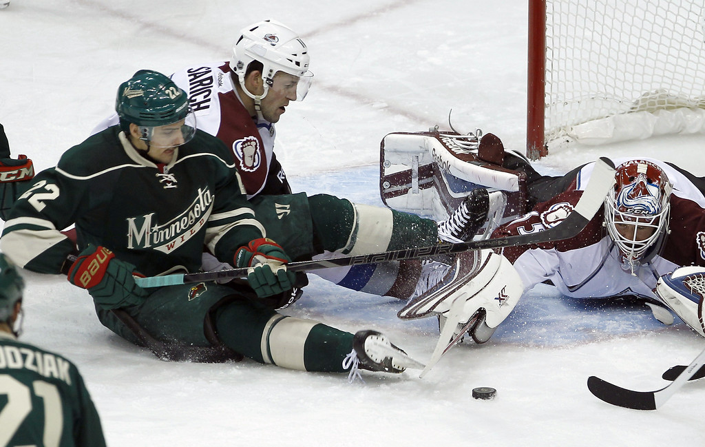 . Colorado Avalanche goalie Jean-Sebastien Giguere, right, uses his stick to get the puck away from Minnesota Wild right wing Nino Niederreiter (22), of Switzerland, as  Avalanche defenseman Cory Sarich watches during the second period of an NHL hockey game in St. Paul, Minn., Friday, Nov. 29, 2013. (AP Photo/Ann Heisenfelt)