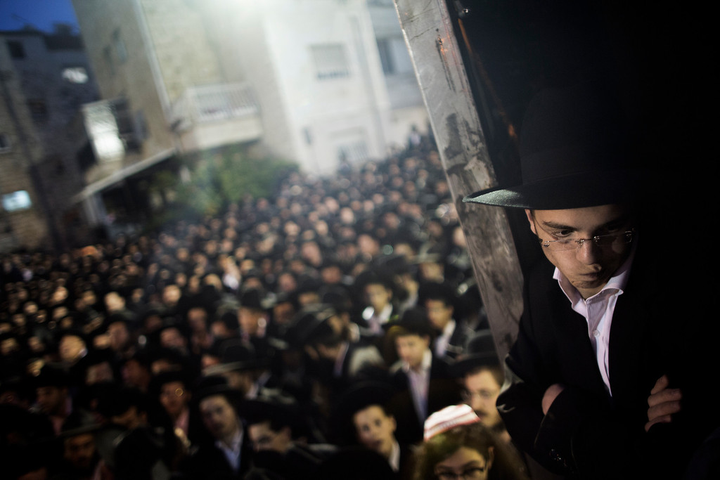 """. An Ultra Orthodox Jew looks on 16, 2013 during a protest in front of the main army recruitment office in Jerusalem to demonstrate against any plans to make them undergo military service, a police spokesman said. Protesters also prayed and chanted \""""the Torah above everything!\"""" referring to Jewish religious law, and \""""the army will not take yeshiva (religious seminary) pupils.\""""  MARCO LONGARI/AFP/Getty Images"""