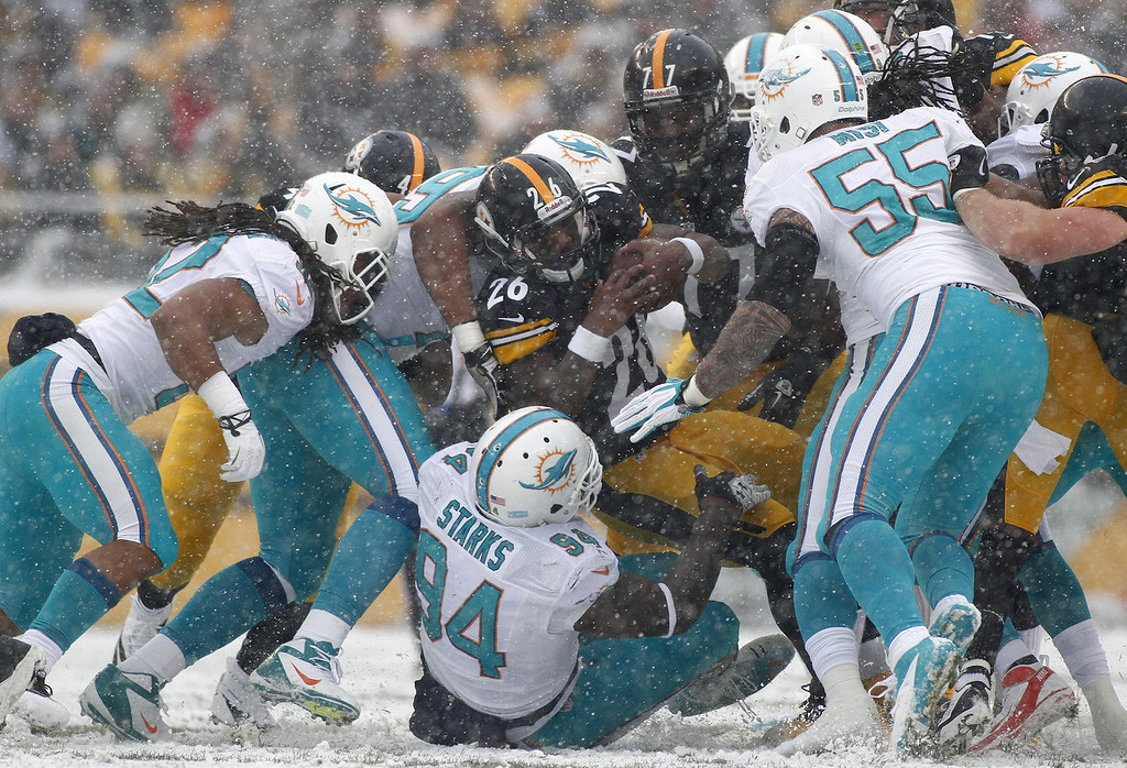 . Le\'Veon Bell #26 of the Pittsburgh Steelers is tackled by Randy Starks #94 of the Miami Dolphins during the game on December 8, 2013 at Heinz Field in Pittsburgh, Pennsylvania. (Photo by Justin K. Aller/Getty Images)